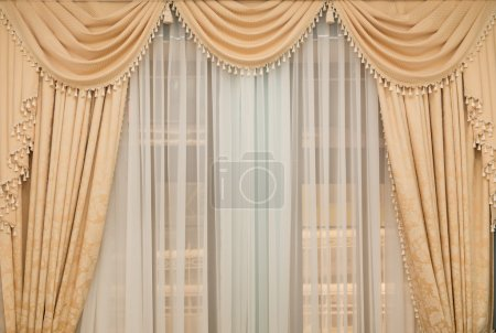 Photo pour Rideau beige classique suspendu à une fenêtre - image libre de droit
