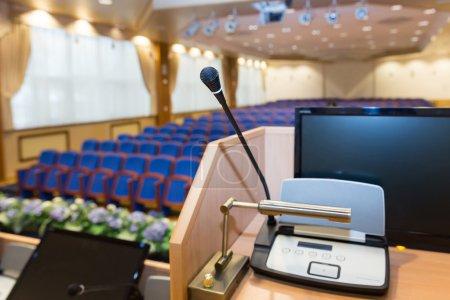 Photo pour Rostre avec microphone et ordinateur dans la salle de conférence - image libre de droit