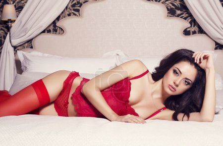 Photo for Sexy woman with black hair in lingerie and pantyhose lying in the bed - Royalty Free Image