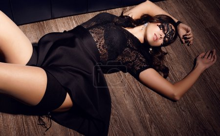 Photo for Sexy glamour woman with dark hair with lace mask on the face lying on the wood  floor - Royalty Free Image
