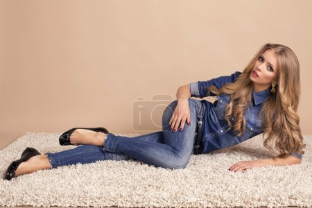beautiful model with blond hair in jeans clothes lying on the carpet