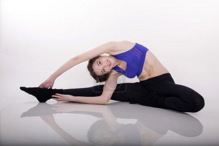 Beautiful woman making stretching at white studio