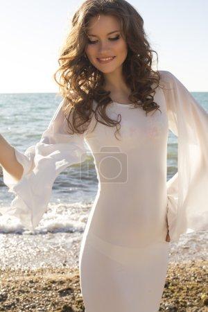Beautiful girl in white dress posing on the beach