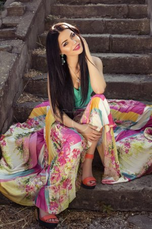 beautiful elegant woman in colorful dress posing at park