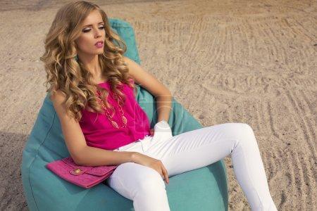 Photo pour Photo de mode de sexy belle fille en vêtements colorés avec accessoires relaxant sur chaise de plage - image libre de droit