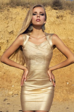 sexy girl with long blond hair in gold dress posing on beach