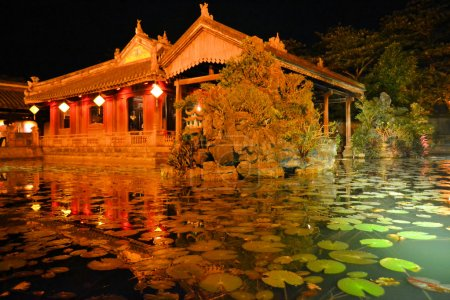 Wooden garden house with pond at night