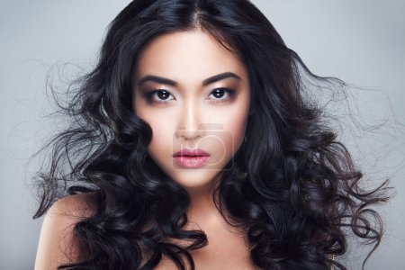 Young and beautiful asian woman with curly hair. Pink lips. Black eyes.