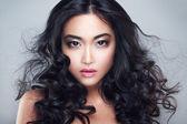 Mladá a krásná asijská žena s kudrnatými vlasy