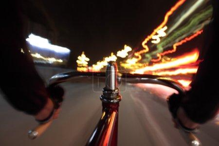 Photo pour Longue exposition prise à partir d'une caméra fixée sur un vélo à engrenages fixes. Au premier plan un gros plan du guidon . - image libre de droit