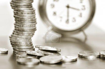 Photo pour Une pile de pièces de monnaie et réveil noir et blanc - image libre de droit