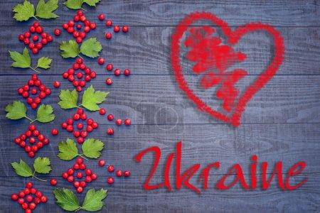 Photo pour Motif ukrainien de baies et feuilles de Viburnum sur le fond en bois sombre - image libre de droit
