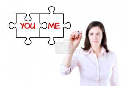 Businesswoman drawing a You and Me puzzle love concept on the virtual screen. Isolated on white.