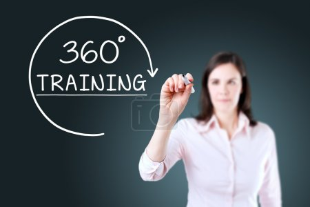 Businesswoman drawing a 360 degrees Training concept on the virtual screen. Blue background.