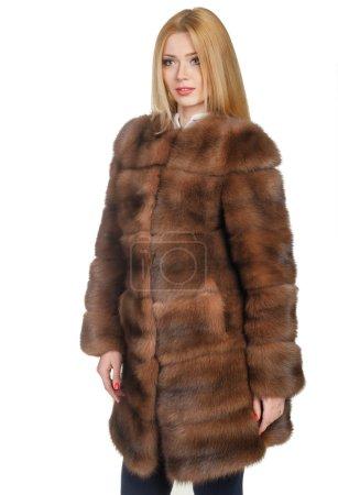 Photo pour Belle jeune fille dans un manteau de fourrure sur fond blanc - image libre de droit