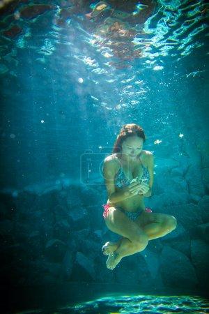 Photo pour Jeune fille nageant sous l'eau bleue . - image libre de droit