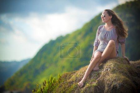 Photo pour Jeune fille assise sur la plage, lunettes de soleil - image libre de droit
