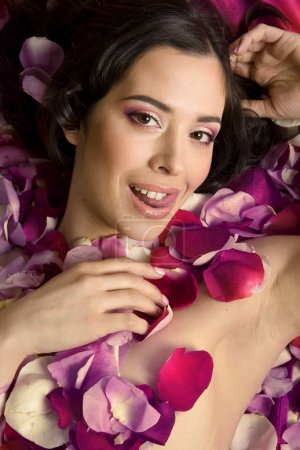 Photo pour Belle jeune femme brune Dans les pétales de rose gros plan - image libre de droit