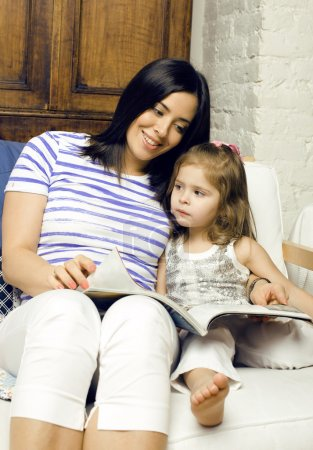Portrait of mother and daughter reading