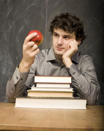 The young emotional student with the books and red apple in class room