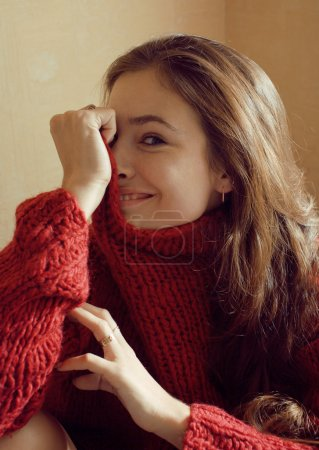 Adorable young woman in sweater at home smiling