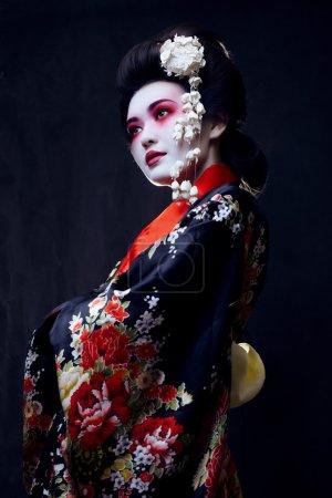geisha in kimono on black