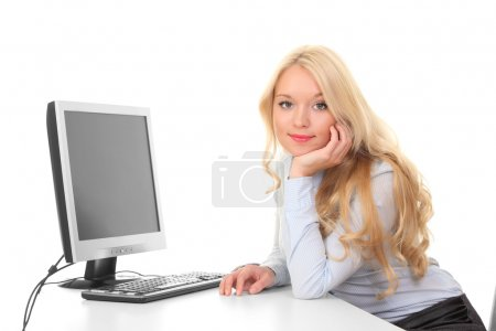 Young cute girl behind a desk with a computer and a monitor