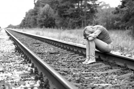 Photo pour Bouleversé fille assis sur les rails - image libre de droit