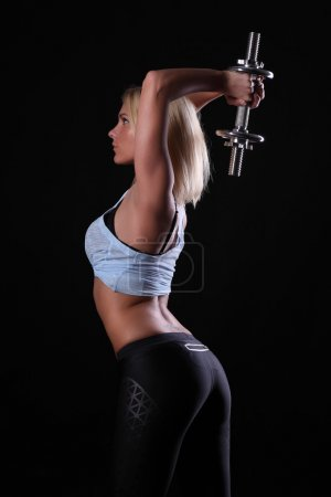 Beautiful sporty woman working out with dumbbells .