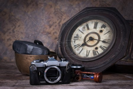 Group of objects on wood table. antique wooden clock, hourglass,