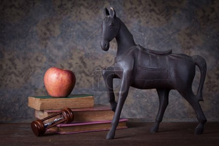 Group of objects on wood table. old wood horse, hourglass, old b