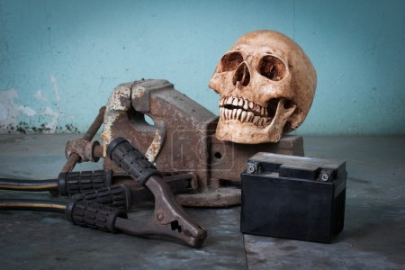 Human skull, bench vise, jumper cable