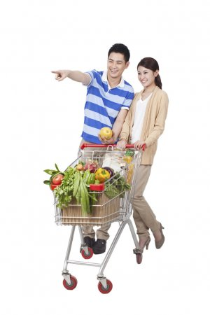 Photo for Young Couple Grocery Shopping on white background - Royalty Free Image