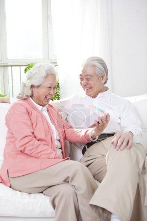 Senior couple holding gift box