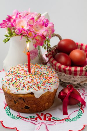 Easter cake with a lit candle, jug with flowers and painted eggs