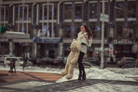 Photo pour Triste belle fille en ville qui vaut la peine d'attendre elle tient un ours . - image libre de droit