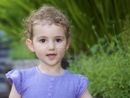 Young child in garden. A pretty girl, toddler, wearing a lilac purple top. Head and shoulders shot, with green backdrop of garden. She has blonde curly hair and a good expression.