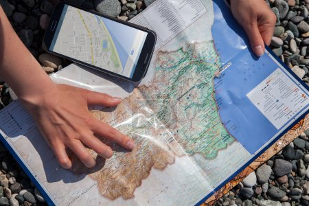 Photo for Planning a journey. Hand pointing a map and using a Mobile Navigation App - Royalty Free Image