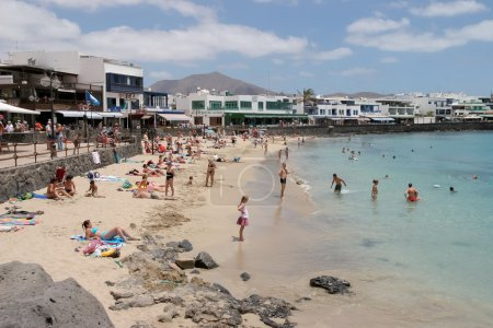 People enjoying the beach and sea at Puerto del Carmen Lanzarote