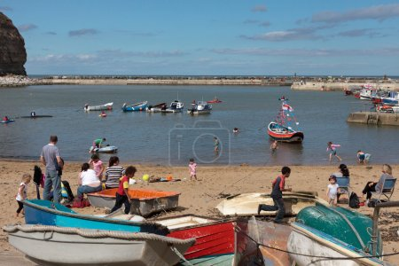 People enjoying themselves in Staithes harbour North Yorkshire