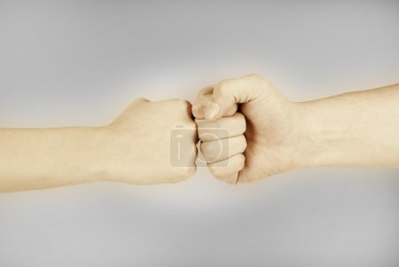 Two hands: man and woman, isolated on grey