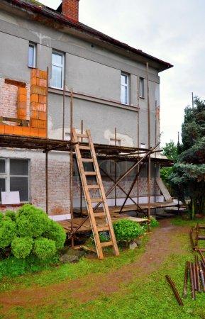 Photo pour Échafaudage sur la maison, reconstruction, nouvelles fenêtres - image libre de droit
