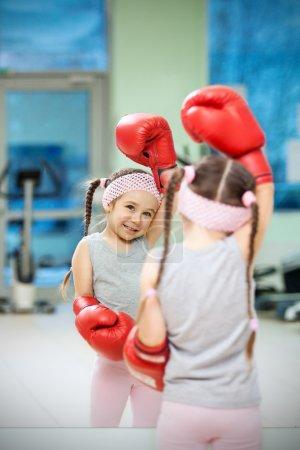 Photo pour Kid dans les gants de boxe près de miroir - image libre de droit