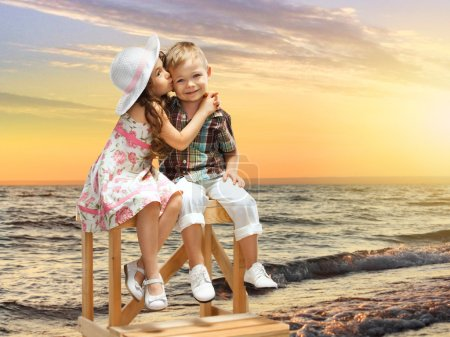 little girl kissing boy on sea landscape at sunset