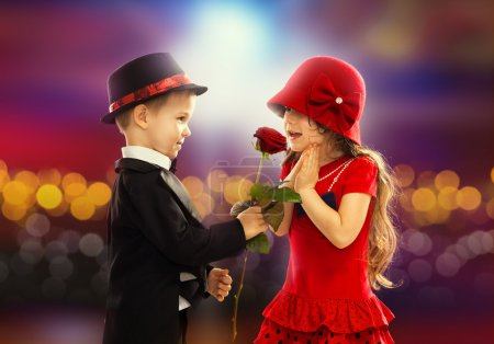 Lovely little boy giving a rose to girl