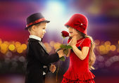 Lovely little boy giving a rose to girl