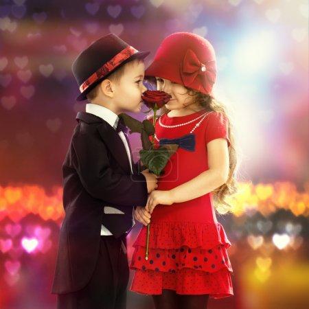 Photo pour Beau petit garçon donnant une rose à la fille à la mode et son excité - image libre de droit
