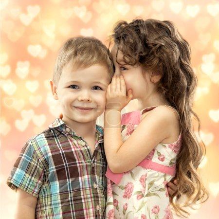 Little girl whispering something to boy