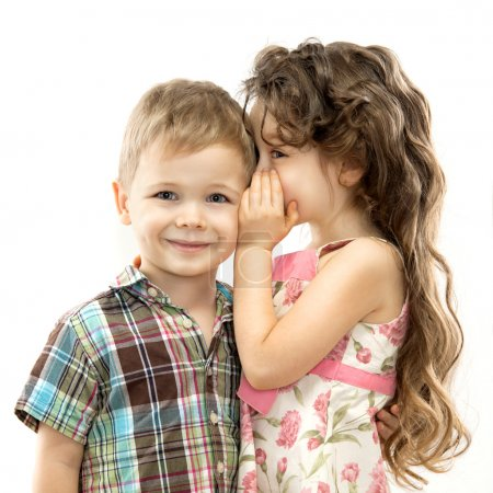 Little girl whispering something to boy