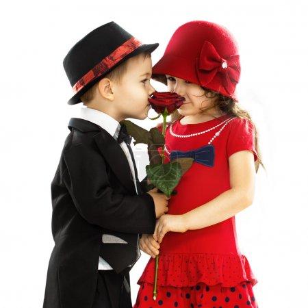 Photo pour Charmant petit garçon donnant une rose à la fille à la mode et son excité. Concept d'amour. Isolé sur fond blanc - image libre de droit